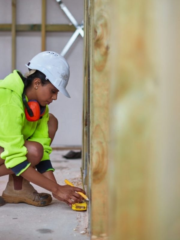Full length of construction worker using tape measure while working. Female engineer is in reflective clothing. She is crouching on floor at construction site.